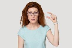 Изумленная рыжеволосая девушка в стеклах показывает небольшой размер что-то стоковые изображения