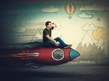 Изумленное летание парня на быстрой ракете смотря руку ко лбу смотря далеко для назначения каникул Возбужденный человек ища  стоковые изображения