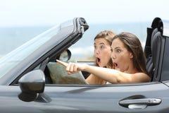 Изумленные девушки в автомобиле указывая прочь Стоковая Фотография RF