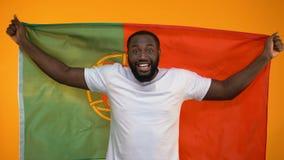 Изумленный Афро-американский болельщик развевая португальский флаг, веселя для победы сток-видео