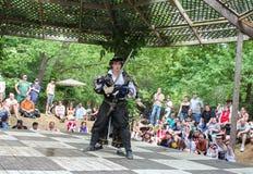 Изумленный боец в средневековых взглядах костюма по мере того как боец женщины прикалывает его с шпагой от заднего и люди наблюда Стоковые Фото