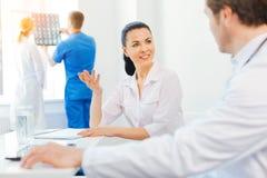 Изумленный женский доктор усмехаясь пока беседующ с коллегой Стоковые Фотографии RF