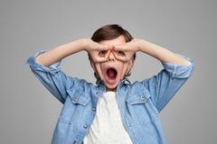 Изумленный мальчик делая жест маски руки стоковое изображение