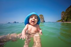 Изумленный младенческий младенец 7 месяцев купает в море в первый раз Солнечный день, папа держит младенца Только руки человека стоковое фото rf