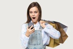 Изумленный покупатель женщины держа хозяйственные сумки смотря экран смартфона стоковые фото