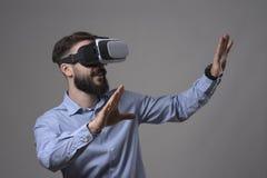 Изумленный шлемофон vr виртуальной реальности молодого взрослого бородатого умного вскользь человека нося показывать руки и смотр Стоковые Изображения