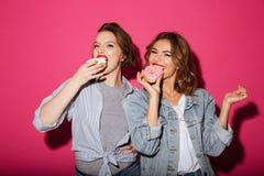Изумлять 2 друзей женщин есть donuts Стоковое фото RF