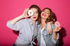 Изумлять 2 друзей женщин есть donuts Стоковое Фото