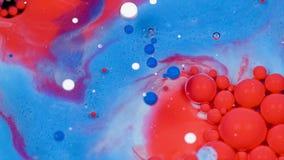 Изумлять красные и голубые пузыри краски на поверхности масла Краска в масле акции видеоматериалы