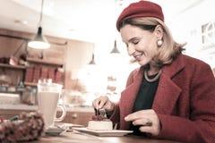 Изумляя белокурая женщина есть вкусный чизкейк стоковые фото