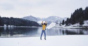 Изумляя взгляд природы больших озера и горы со снежным лесом, очень счастливым туристом бежать с картой перед сток-видео