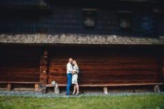 Изумляя пары свадьбы в рубашке embroidereds с пуком цветков на предпосылке деревянного дома стоковые изображения