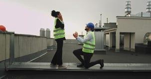 Изумляя предложение на крыше инженера дамы строительной площадки африканского и ее партнер имеют предложение очень сток-видео