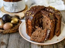 Изумляя торт пасхи шоколада с падениями шоколада и сухие вишни на старой деревянной предпосылке с черными и золотыми яйцами ломти стоковое фото rf