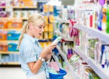 Изумленная девушка на магазине выбирая косметики Стоковое Изображение RF