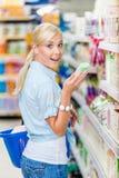 Изумленная девушка на магазине выбирая косметики Стоковая Фотография RF