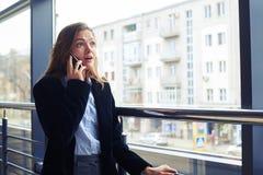 Изумленная женская сторона говоря на телефоне Стоковые Изображения