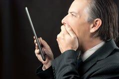 Изумленный бизнесмен смотрит его таблетку Стоковые Изображения RF