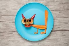 Изумленный кот сделанный из моркови и огурца на плите и таблице Стоковые Изображения