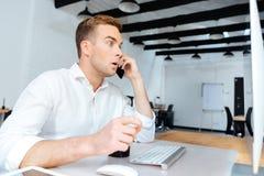 Изумленный кофе молодого бизнесмена выпивая и говорить на сотовом телефоне Стоковая Фотография RF