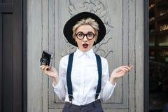 Изумленный фотограф молодой женщины стоя и держа камера фото стоковое изображение rf
