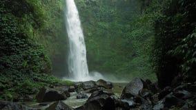 Изумляющ водопад Nungnung, замедляйте жестикулированную падая воду ударяя поверхность воды, некоторые огромные утесы seeable пере акции видеоматериалы