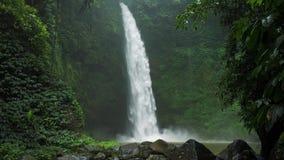 Изумляющ водопад Nungnung, замедляйте жестикулированную падая воду ударяя поверхность воды, некоторые огромные утесы seeable пере видеоматериал