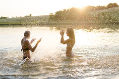 2 изумляя молодых женщины имея потеху в озере Стоковая Фотография