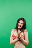 Изумляя усмехаясь брюнет в ярком Swimwear представляя с коктеилем в студии на зеленой предпосылке Стоковое фото RF