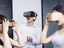 Изумлённые взгляды виртуальной реальности молодых азиатских людей пробуя Стоковые Фото