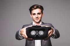 Изумлённые взгляды VR Человек дает, указал изумлённые взгляды виртуальной реальности смотря кино или играя видеоигры изолированны стоковые изображения rf