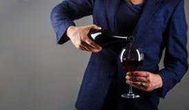 Изысканная бутылка напитка, красный бокал, сомелье, дегустация Официант лить красное вино в стекле Человек сомелье, degustation стоковое фото rf