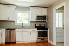 Изысканная кухня отличает белыми шкафами шейкера с мраморными countertops, стоковые фотографии rf