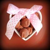 Изысканные трюфеля шоколада на день ` s валентинки Конфета шоколада служила на блюде сформированном сердцем и декоративной ленте Стоковые Фото