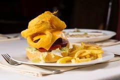 Изысканные фраи Cheeseburger и француза на плите Стоковое фото RF