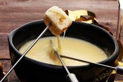 Изысканный швейцарский обедающий фондю на вечере зимы с сортированными сырами на доске наряду с heated баком фондю сыра с 2 Стоковые Фотографии RF