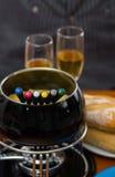 Изысканный швейцарский обедающий фондю с сортированными сырами и heated баком фондю сыра при красочные вилки окуная внутрь Стоковое Изображение RF