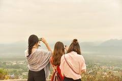 3 из азиатских дам наслаждаются горным видом, используют умное captur телефона Стоковые Изображения