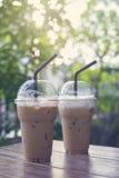 2 из взятия прочь заморозили кофейную чашку положенную на деревянный стол на кафе кофе запачканная предпосылка Селективный фокус Стоковая Фотография RF