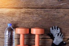 2 из гантелей и защитных перчаток на деревянном поле Стоковое Изображение