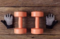 2 из гантелей и защитных перчаток на деревянном поле Стоковые Фото