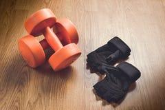 2 из гантелей и защитных перчаток на деревянном поле Стоковая Фотография RF