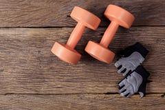 2 из гантелей и защитных перчаток на деревянном поле Стоковое Фото