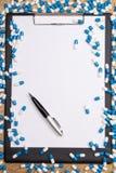 Излечите пилюлек, доски сзажимом для бумаги и ручки на деревянном столе стоковые фотографии rf