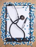 Излечите таблеток, доски сзажимом для бумаги, стетоскопа и ручки на деревянном столе стоковые фотографии rf
