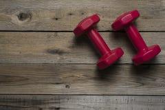2 из красных гантелей на деревянной таблице Стоковые Фото