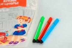 3 из отметки лежа рядом с тетрадью для ребят школьного возраста, крася ? стоковые изображения