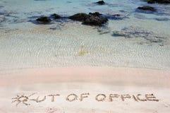 ИЗ ОФИСА написанного на песке на красивом пляже, синь развевает в предпосылке стоковые фото