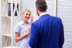2 из привлекательных бизнесменов, стоящ рядом друг с другом, держащ чашки, усмехаясь положение на офисе усмехаться стоковое фото rf