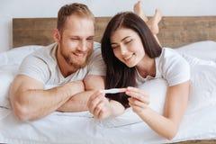 Излучающие пары смотря тест на беременность в кровати стоковое фото